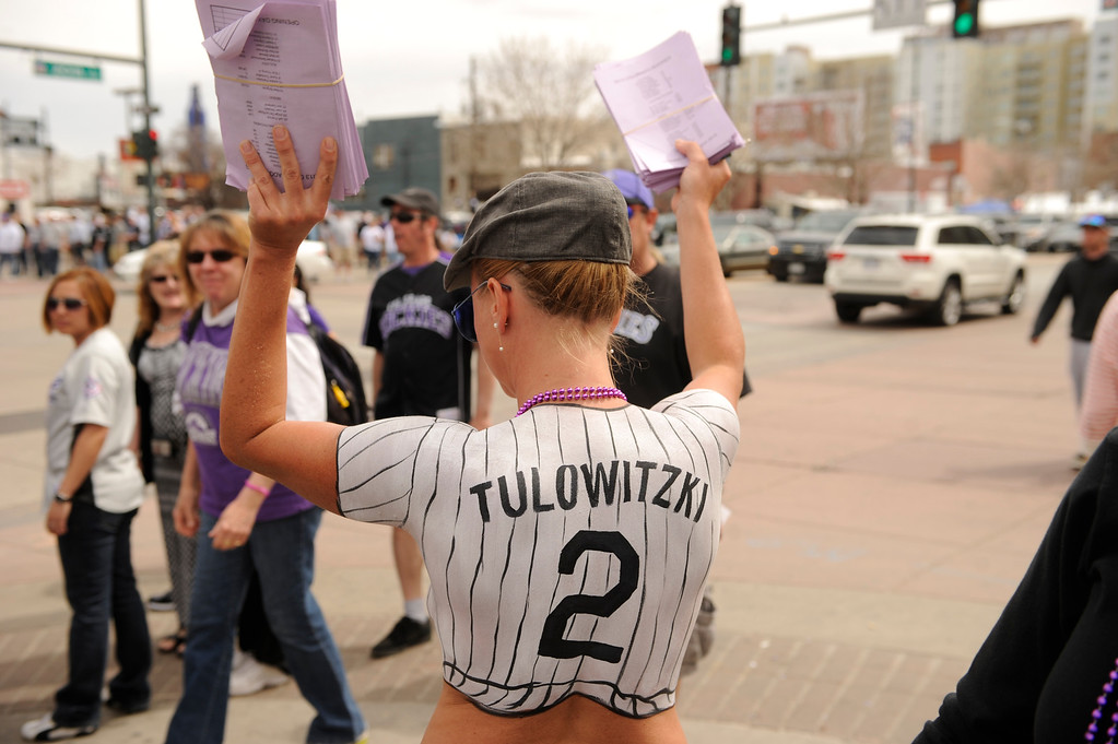 . Emily Thompson gives away rosters for tips while sporting a body paint in the form of a Rockies jersey outside the stadium.  (Photo by Karl Gehring/The Denver Post)