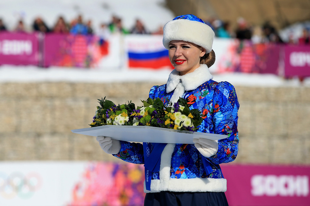 . A flower bearer presents bouquets during the flower ceremony for the Cross Country Men\'s 4 x 10 km Relay during day nine of the Sochi 2014 Winter Olympics at Laura Cross-country Ski & Biathlon Center on February 16, 2014 in Sochi, Russia.  (Photo by Richard Heathcote/Getty Images)