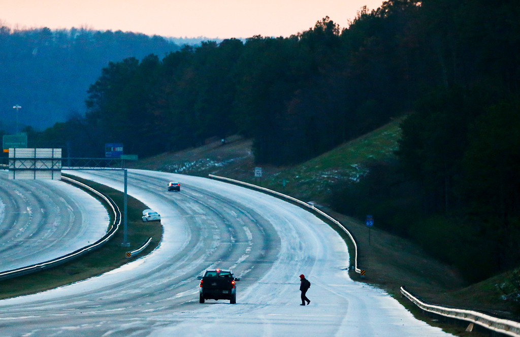 . A person catches a ride on the icy highway after leaving their car on the side of the road, Saturday, Jan. 7, 2017, near Birmingham, Ala.  Forecasters are saying travel could be a problem through Saturday, and some flights already have been canceled because of the weather. (AP Photo/Brynn Anderson)