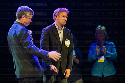 Joe Fugere of Tutta Bella (center) responds after his company received the number one ranking in the Pride Top 25 LGBTQ business list makers at the Puget Sound Business Journal's The Business Of Pride at the Paramount Theatre in Seattle on Thursday, May 26, 2016. (BUSINESS JOURNAL PHOTO | Dan DeLong)
