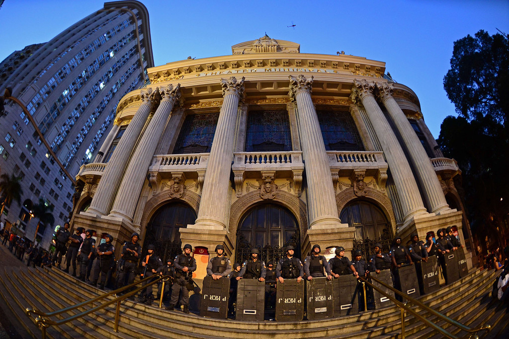 ". Riot police officers stand guard outside the National Theatre in Rio de Janeiro on July 11, 2013 as Brazilian workers march in a day of industrial action called by major unions to press demands for better work conditions. Demonstrators on Thursday blocked roads and staged protest rallies across the country on the ""National Day of Struggles\"" which was called by the country\'s five leading labour federations during last month\'s mass street protests to demand better public services and an end to endemic corruption. CHRISTOPHE SIMON/AFP/Getty Images"