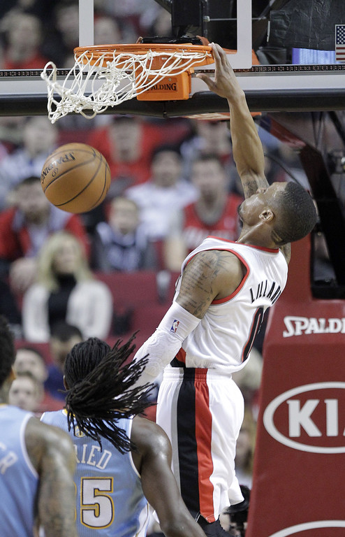 . Portland Trail Blazers guard Damian Lillard, right, scores over Denver Nuggets forward Kenneth Faried during the first half of an NBA basketball game in Portland, Ore., Saturday, March 1, 2014. (AP Photo/Don Ryan)