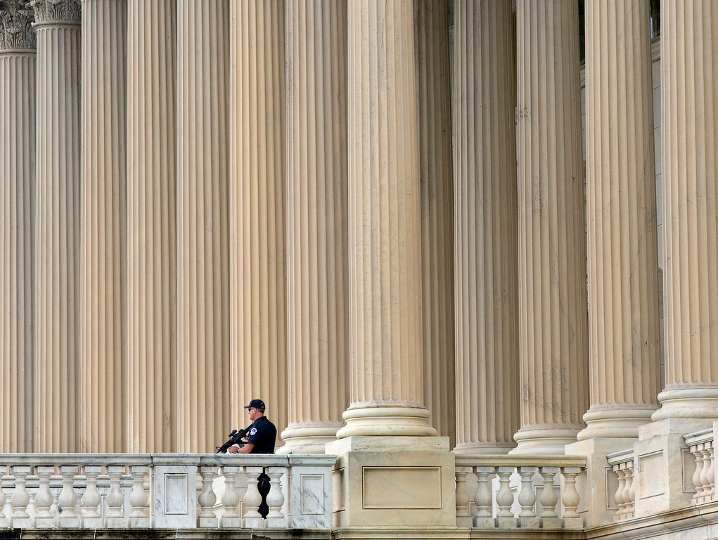 . U.S. Capitol Police personnel keep watch on the East Plaza of the Capitol as the investigation continues to the shooting at the nearby Washington Navy Yard  Monday, Sept. 16, 2013, in Washington. At least one gunman opened fire inside a building at the Washington Navy Yard on Monday morning.  (AP Photo/J. Scott Applewhite)