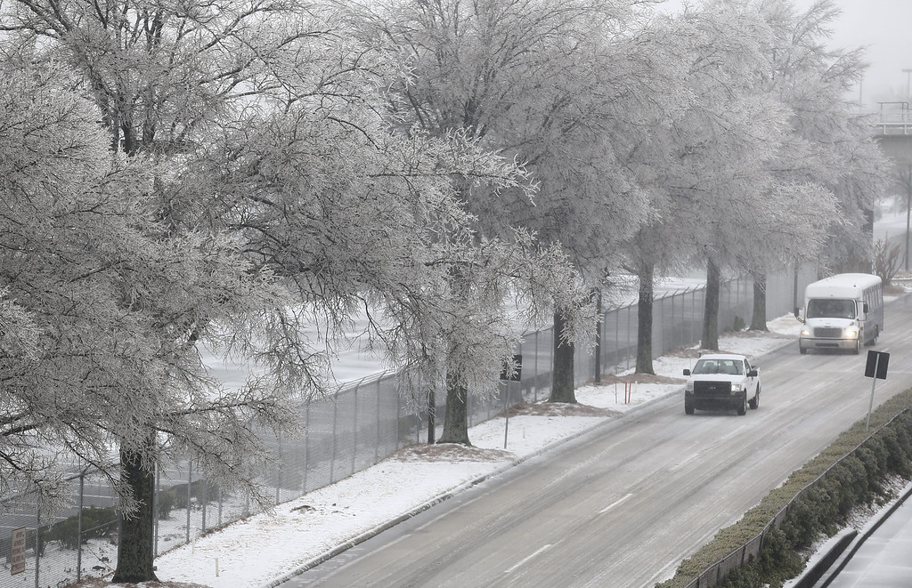 . Vehicles drive under trees covered in ice on a access road at Hartsfield-Jackson Atlanta International Airport during a severe winter storm in Atlanta, Georgia, USA, 12 February 2014. More than 1,800 flights have been cancelled at the airport. Ice and snow in the metro Atlanta area is expected to make travel treacherous and cut electricity to thousands of customers.  EPA/ERIK S. LESSER