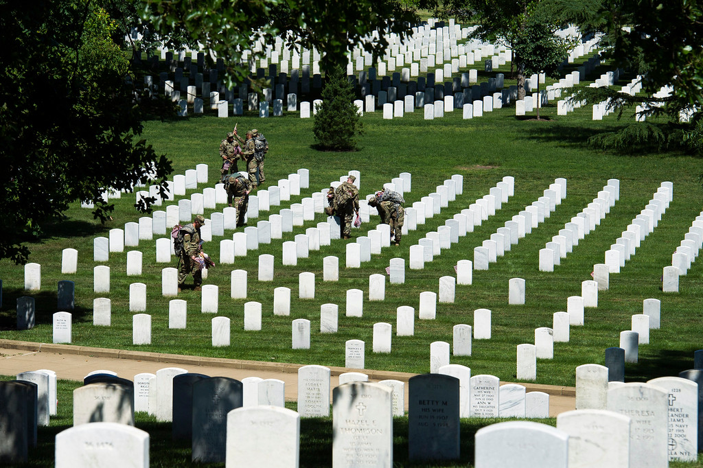. Members of the Army 3d U.S. Infantry Regiment, The Old Guard, place flags at the headstone of fallen military members during its annual Flags In ceremony at Arlington National Cemetery, May 24, 2018, in Arlington, Va. (AP Photo/Cliff Owen)