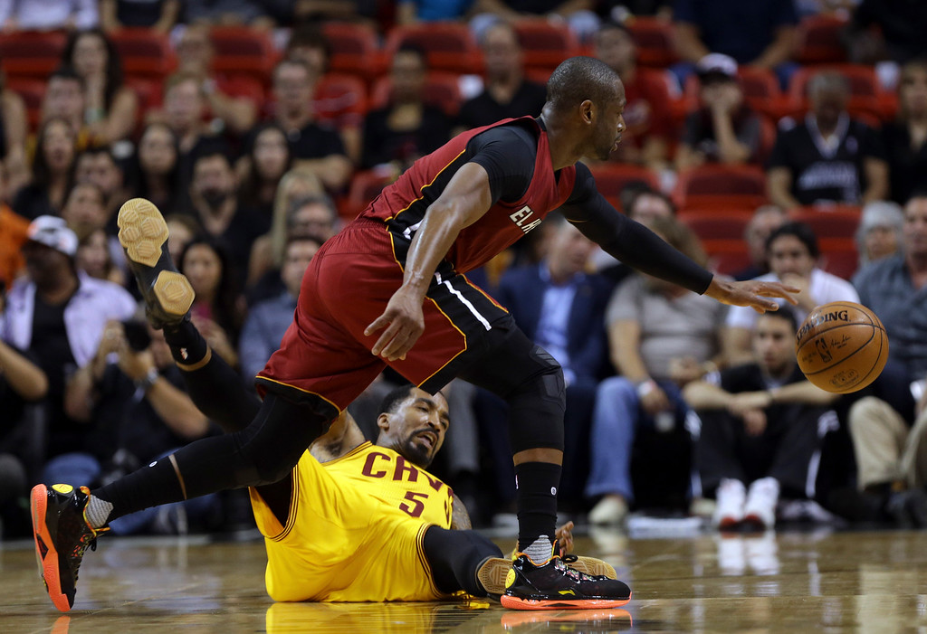 . Miami Heat guard Dwyane Wade loses control of the ball as Cleveland Cavaliers guard J.R. Smith (5) falls to the floor during the first half of an NBA basketball game, Saturday, March 19, 2016, in Miami. (AP Photo/Lynne Sladky)
