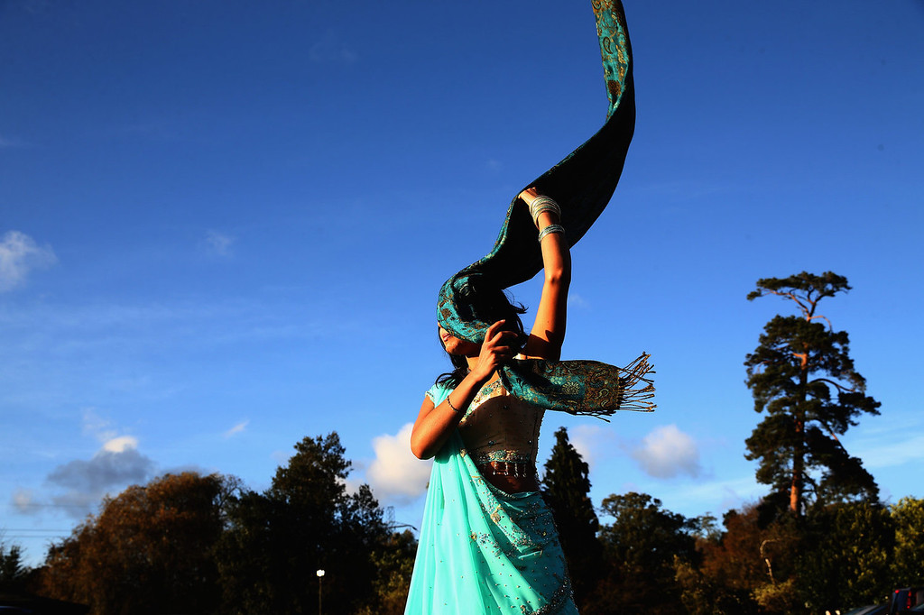 . A woman struggles with her scarf in high winds during Diwali celebrations at Bhaktivedanta Manor on November 3, 2013 in Watford, United Kingdom. The festival is an opportunity for Hindus to honor Lakshmi, the goddess of wealth and other gods. Leicester\'s celebrations are one of the biggest in the world outside India.  (Photo by Dan Kitwood/Getty Images)