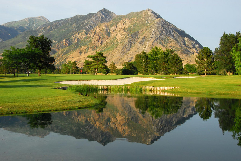 7/6/07 – It has been 100 degrees or hotter for days but I went out and played 9 holes of golf after work anyway. There was no wind, which made this reflection of the mountains on the pond possible.