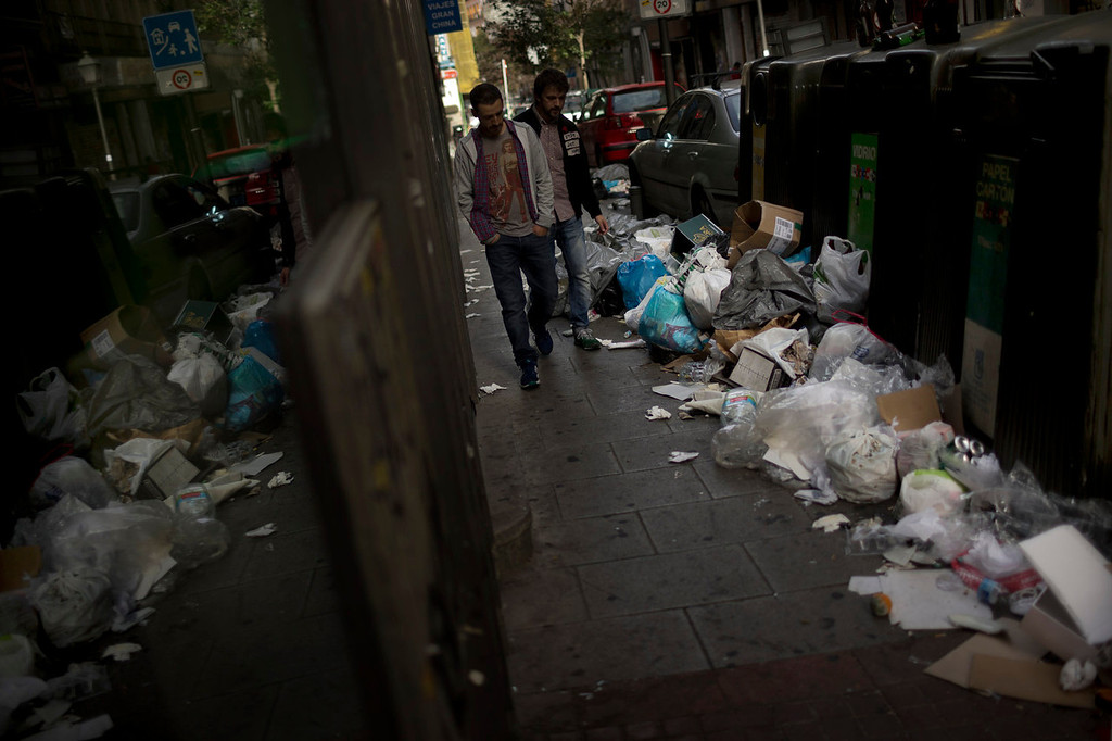 . A couple walks by containers already piled up with trash bags during the sixth day of a garbage collectors strike, in Madrid, Sunday, Nov. 10, 2013. Street cleaners and garbage collectors who work in the city\'s public parks walked off the job in a strike called by trade unions to contest the planned layoff of more than 1,000 workers. Madrid\'s municipal cleaning companies, which have service supply contracts with the city authorities, employ some 6,000 staff. (AP Photo/Daniel Ochoa de Olza)