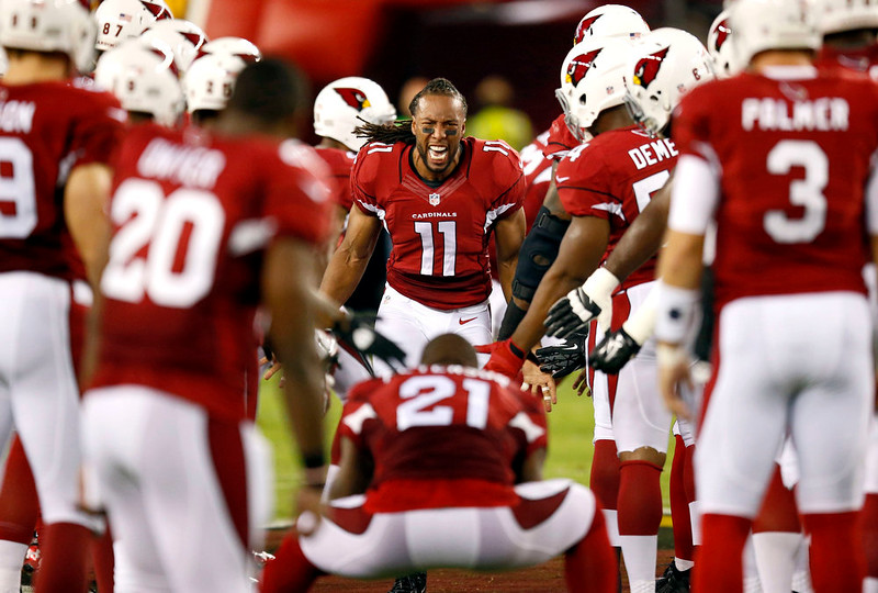 . Arizona Cardinals wide receiver Larry Fitzgerald (11) runs towards Patrick Peterson (21) as he takes the field prior to an NFL football game against the San Diego Chargers, Monday, Sept. 8, 2014, in Glendale, Ariz. (AP Photo/Ross D. Franklin)