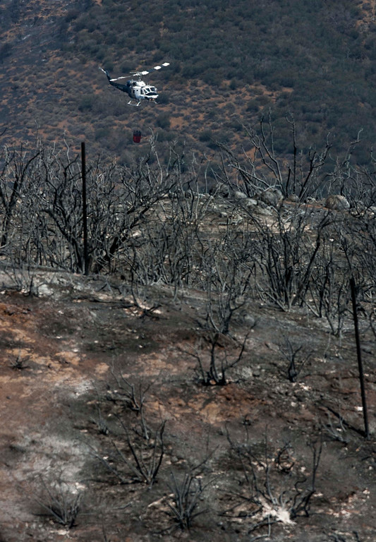 . A helicopter positions itself for a drop on a hotspot near Point Mugu, Calif., Saturday, May 4, 2013. High winds and withering hot, dry air were replaced by the normal flow of damp air off the Pacific, significantly reducing fire activity. (AP Photo/Ringo H.W. Chiu)