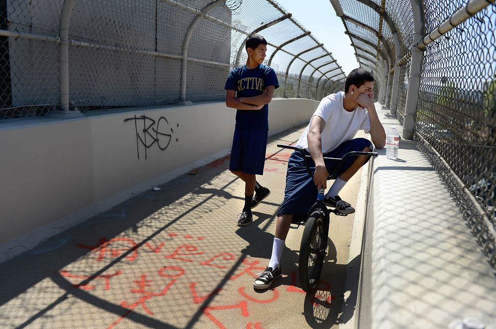 ". On a pedestrian bridge Cesar ""Popper\"" Meza, 15, left, and his friend watch California Highway Patrol officers and the Los Angeles County Coroner investigate a fatal motorcycle crash on the westbound 60 Freeway east of Hacienda Boulevard in Hacienda Heights Tuesday, March 26, 2013.(SGVN/Staff Photo by Sarah Reingewirtz)"