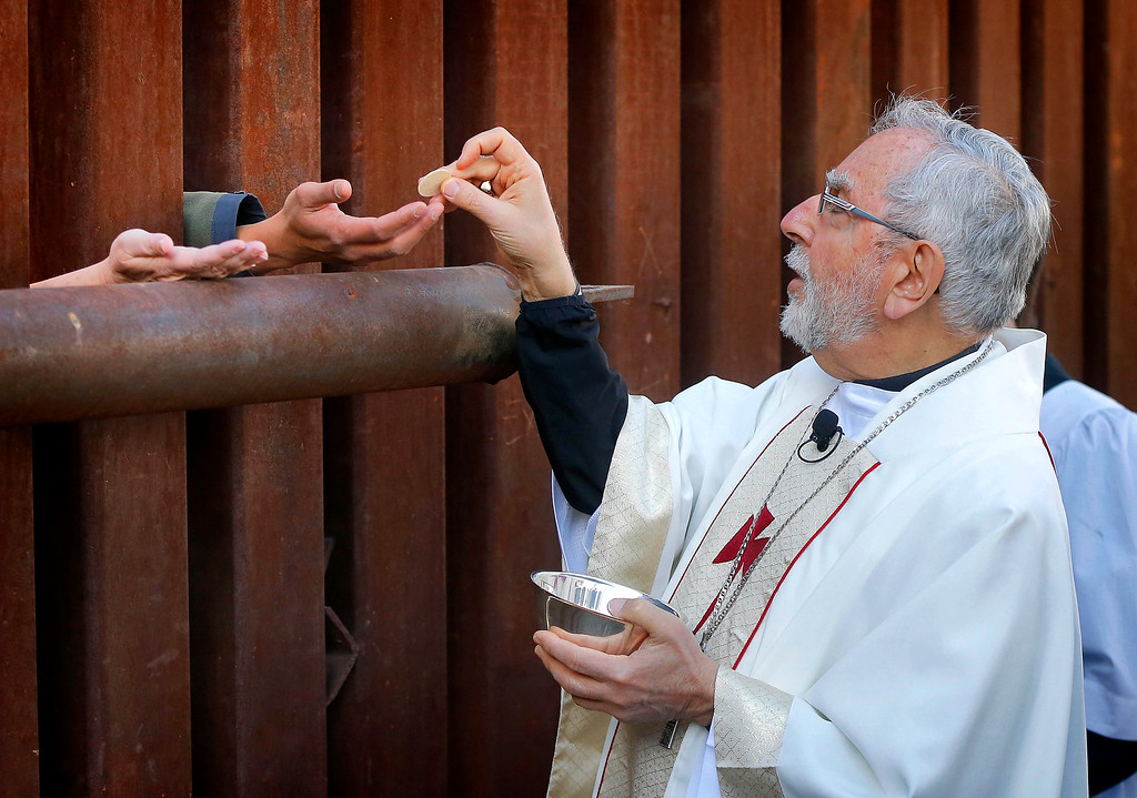 . Most Reverend Gerald F. Kicanas, Bishop of Tucson, offers communion to people on the Mexican side of the international border, Tuesday, April 1, 2014, in Nogales, Ariz. Kicanas and Boston Archdiocese Cardinal Sean O\'Malley, along with several Bishops who serve along the U.S./Mexico border, were visiting the border town to bring awareness to immigration reform and to remember those who have died trying to cross the border in years past. (AP Photo/Matt York, File)