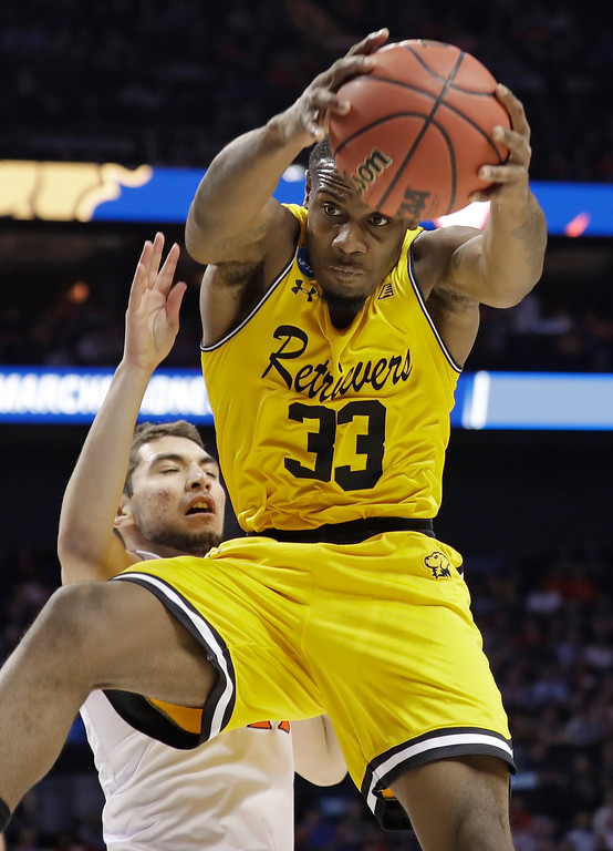 . UMBC\'s Arkel Lamar (33) grabs a rebound in front of Virginia\'s Ty Jerome during the first half of a first-round game in the NCAA men\'s college basketball tournament in Charlotte, N.C., Friday, March 16, 2018. (AP Photo/Gerry Broome)