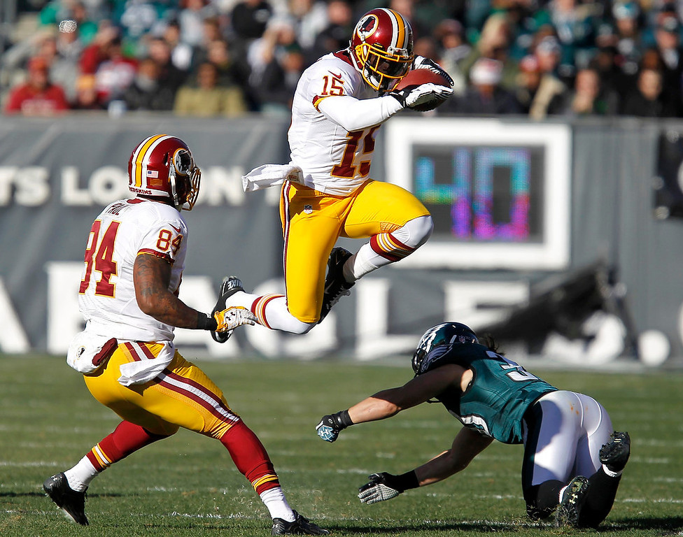 . Washington Redskins receiver Joshua Morgan (15) leaps to avoid a tackle from Philadelphia Eagles safety Colt Anderson (30) as Redskins\' Niles Paul (84) follows the play during the second quarter of their NFL football game in Philadelphia, Pennsylvania, December 23, 2012. REUTERS/Tim Shaffer