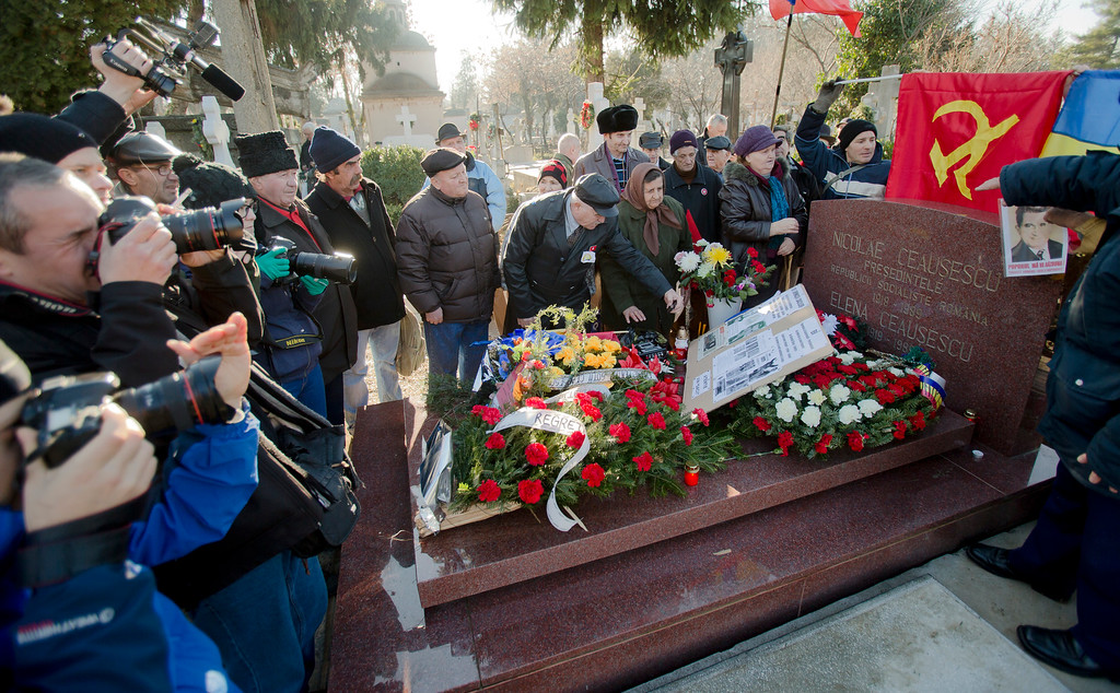 . Media, rivaling in numbers the  communism nostalgics, crowd around the grave of Romanian communist dictator Nicolae Ceausescu, in Bucharest, Romania,  Thursday, Dec. 25, 2014, 25 years after he and his wife Elena were executed by firing squad on Christmas day 1989. Romanians, especially those of a more senior age, have mixed feelings about the former dictator and his rule, 25 years after his execution, with many remembering predominantly the positive aspects, like the social security, of the communist times and not focusing on the extreme economic hardships and lack of basic human rights of that period.  (AP Photo/Vadim Ghirda)