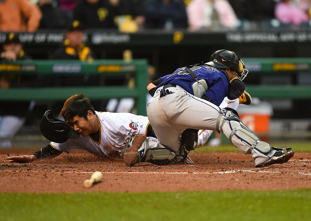 . PITTSBURGH, PA - MAY 21:  Jung Ho Kang #27 of the Pittsburgh Pirates is tagged out at home plate by Tony Wolters #14 of the Colorado Rockies during the fourth inning on May 21, 2016 at PNC Park in Pittsburgh, Pennsylvania.  (Photo by Joe Sargent/Getty Images)