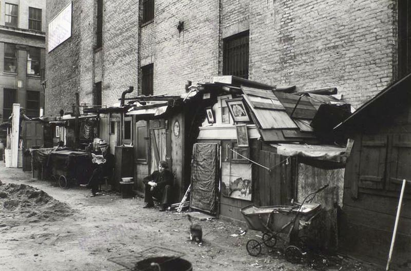 Huts_and_unemployed_in_West_Houston_and_Mercer_St_by_Berenice_Abbott_in_Manhattan_in_1935.jpg