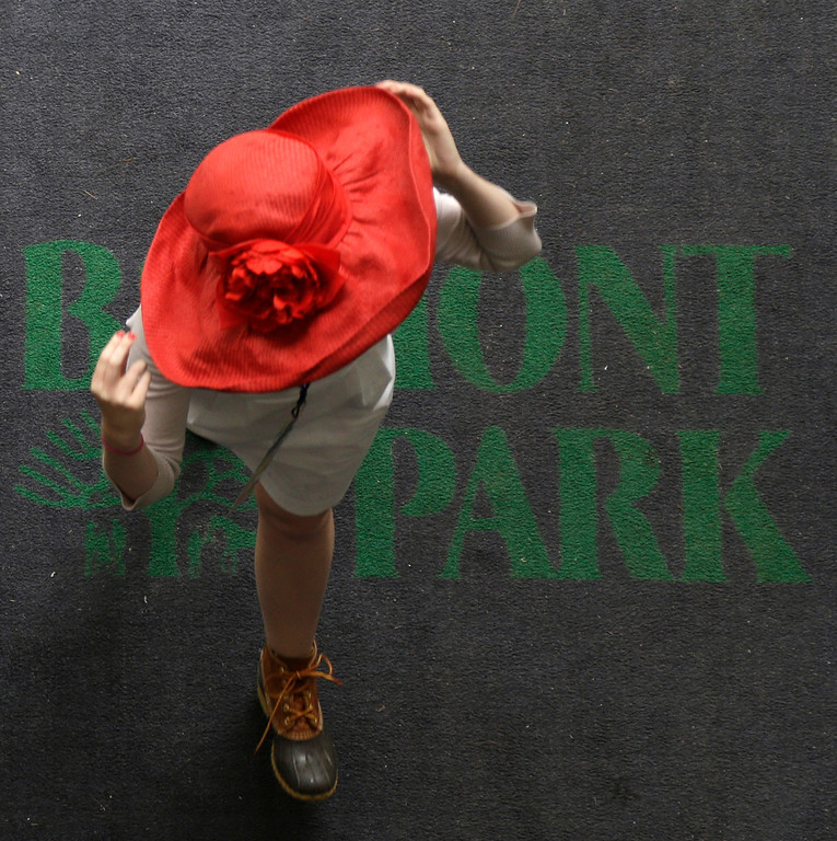 . A woman walks over a mat with the Belmont Park logo before the Belmont Stakes horse race, Saturday, June 8, 2013, in Elmont, N.Y. (AP Photo/Seth Wenig)