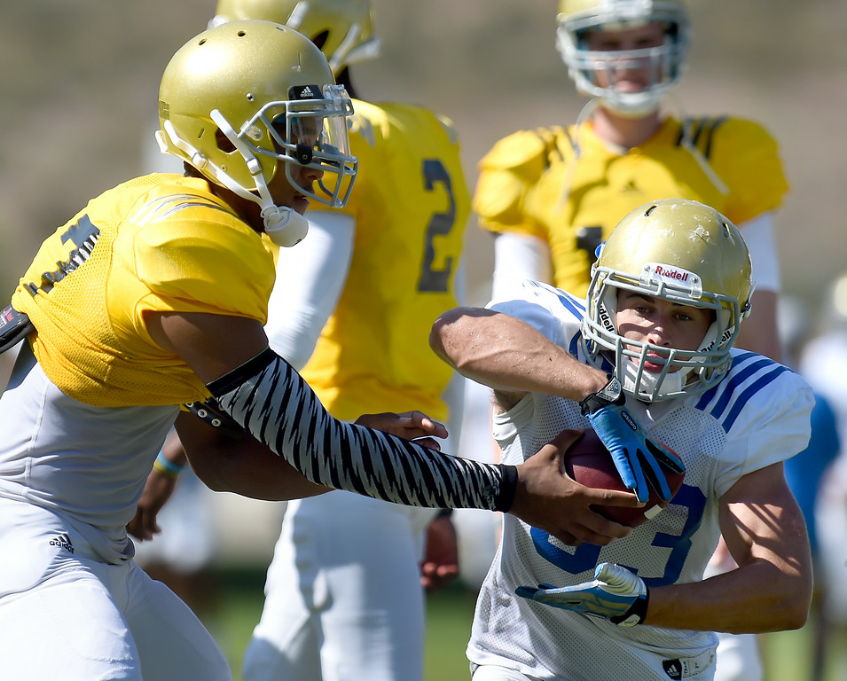. Quarterback Brett Hundley passes the ball off to Steven Manfro during the UCLA Bruins football practice at Cal State San Bernardino in San Bernardino, CA, Friday, August 8, 2014. (Photo by Jennifer Cappuccio Maher/Inland Valley Daily Bulletin)