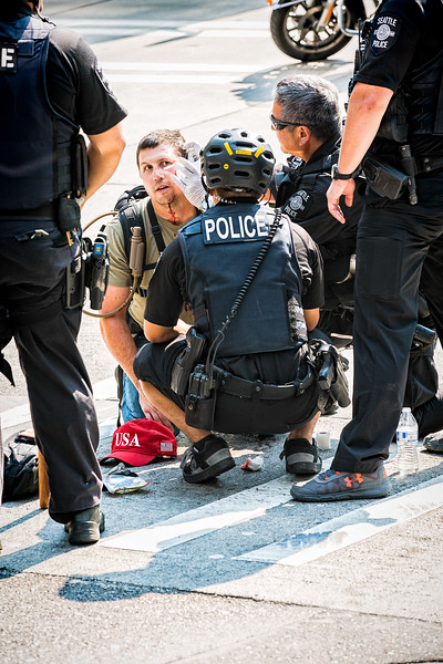 "Police tend to the wounds of a Trump supporter at the ""Liberty or Death"" rally.  Counterprotesters taunted him by bullhorn for allowing himself to be patched up by police."