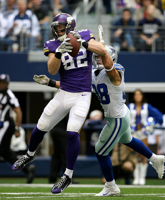 . Minnesota Vikings tight end Kyle Rudolph (82) comes down with a pass in front of Dallas Cowboys\' Jeff Heath (38) before running it in for a score in the second half of an NFL football game, Sunday, Nov. 3, 2013, in Arlington, Texas. (AP Photo/Tim Sharp)
