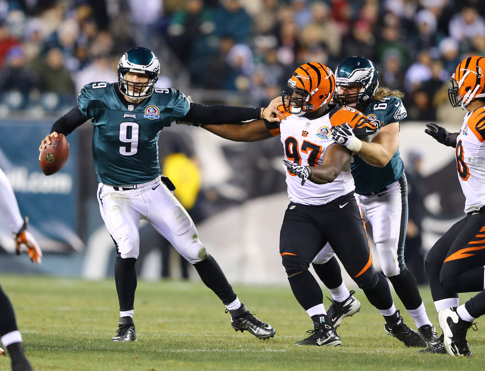 Description of . Nick Foles #9 of the Philadelphia Eagles is pressured by  Geno Atkins #97 of the Cincinnati Bengals during their game at Lincoln Financial Field on December 13, 2012 in Philadelphia, Pennsylvania.  (Photo by Al Bello/Getty Images)