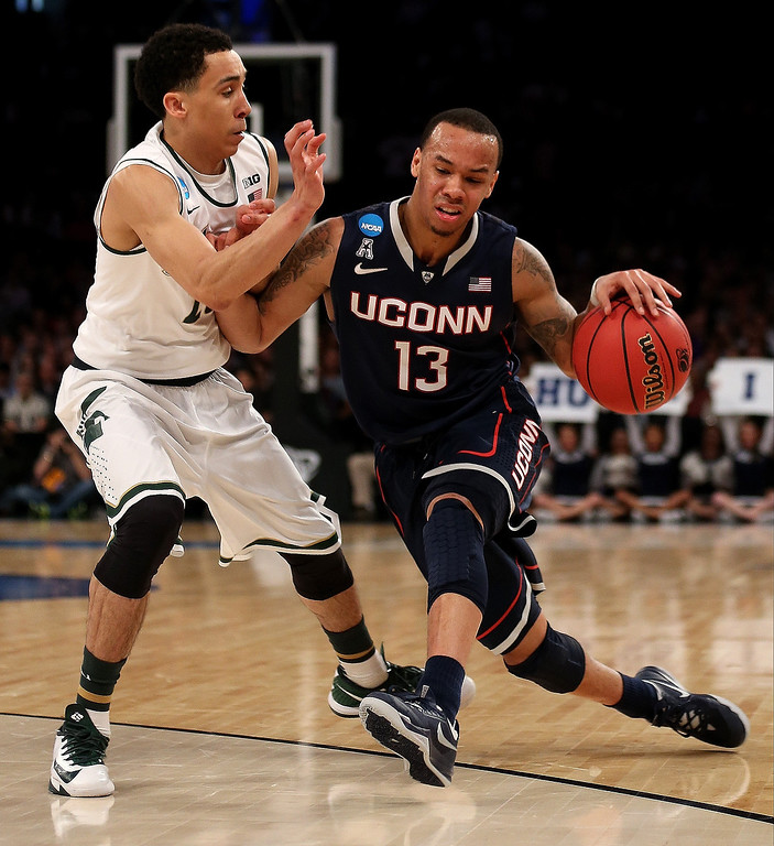 . Shabazz Napier #13 of the Connecticut Huskies handles the ball against Denzel Valentine #45 of the Michigan State Spartans during the East Regional Final of the 2014 NCAA Men\'s Basketball Tournament at Madison Square Garden on March 30, 2014 in New York City.  (Photo by Bruce Bennett/Getty Images)