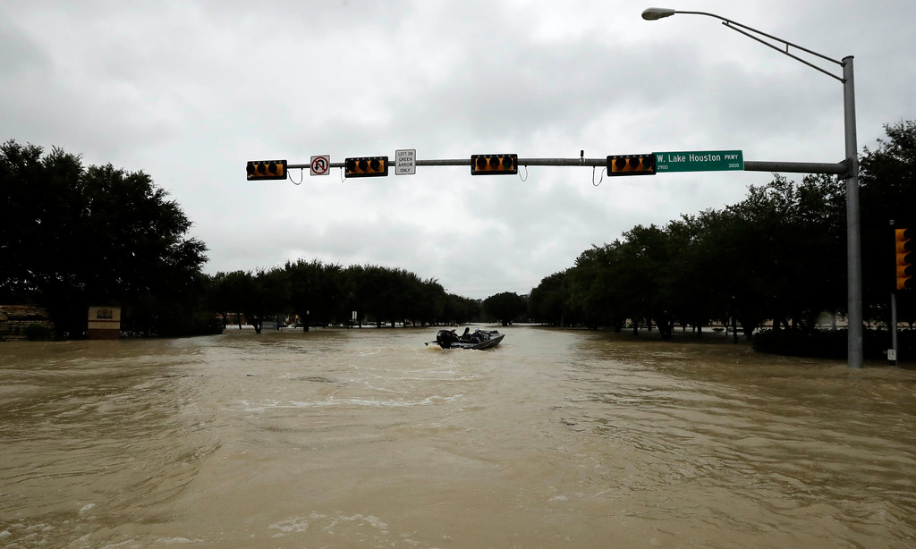 . A boat makes its way up the flooded Lake Houston Parkway as floodwaters from Tropical Storm Harvey rise Tuesday, Aug. 29, 2017, in Kingwood, Texas. (AP Photo/Gregory Bull)
