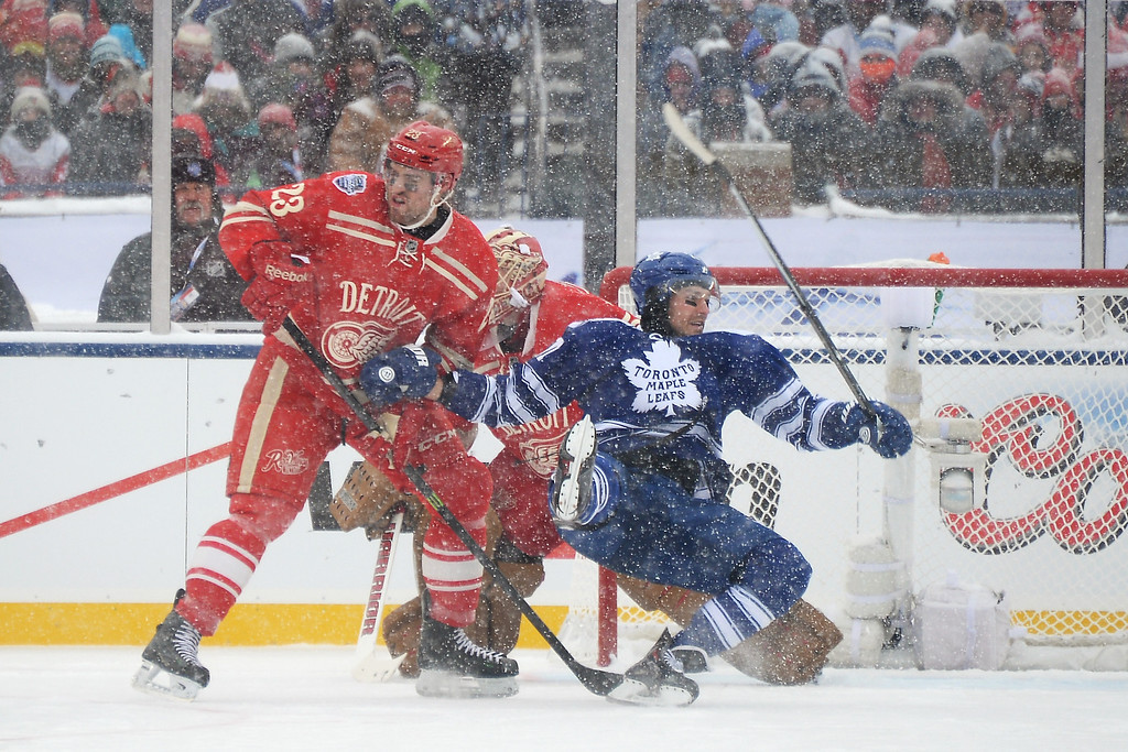 . David Clarkson #71 of the Toronto Maple Leafs falls over the stick of Brian Lashoff #23 of the Detroit Red Wings in the first period during the 2014 Bridgestone NHL Winter Classic on January 1, 2014 at Michigan Stadium in Ann Arbor, Michigan.  (Photo by Jamie Sabau/Getty Images)