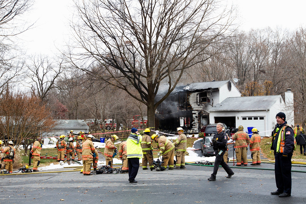 . Montgomery County, Md. firefighters stand outside a house where a small private jet crashed in Gaithersburg, Md., Monday, Dec. 8, 2014. A woman and her two young sons inside the home and three people on the aircraft were killed, authorities said. (AP Photo/Jose Luis Magana)