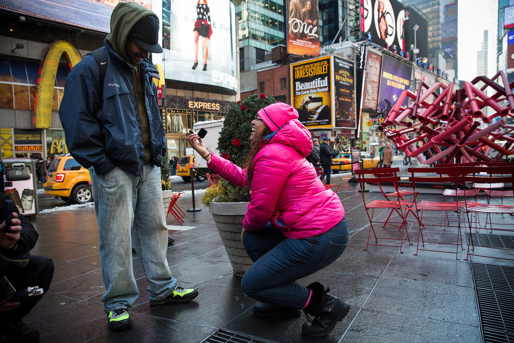 """. Kasunda Smith (R), proposes to her boyfriend of 15 years, Dale Cole in Times Square on February 14, 2014 in New York City.  The proposal was coordinated with clothing company American Eagle, which broadcast \""""Dale, will you marry me?\"""" on the American Eagle screen, however Cole was late to arrive, forcing Smith to propose without the sign. (Photo by Andrew Burton/Getty Images)"""
