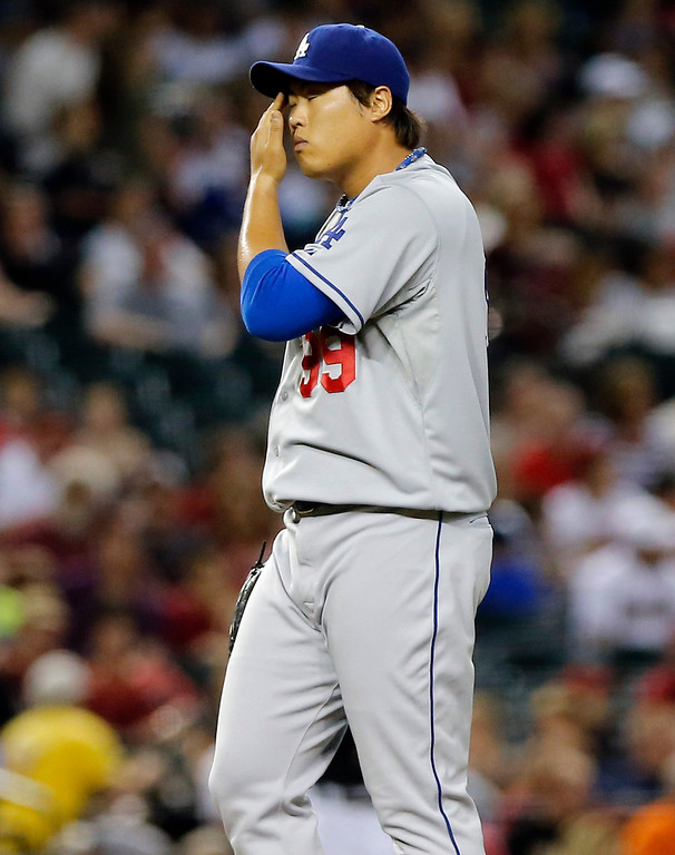 . Los Angeles Dodgers pitcher Hyun-Jin Ryu wipes his face after giving up a home run to Arizona Diamondbacks\' Aaron Hill during the first inning of a baseball game, Wednesday, July 10, 2013, in Phoenix. (AP Photo/Matt York)