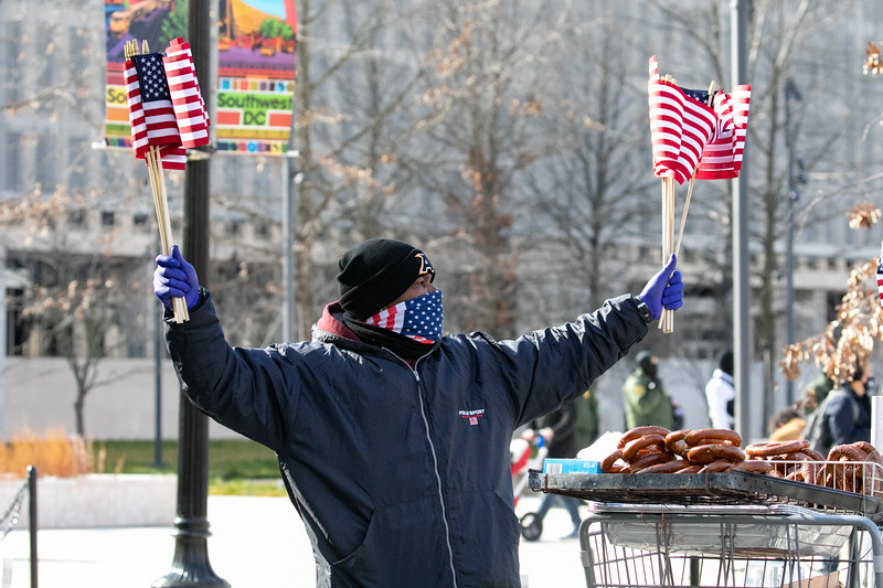 A street vendor sells American flags near a masked group of people gathered near the U.S. Capitol amid a backdrop of National Guard troops watch the inauguration live on their phones