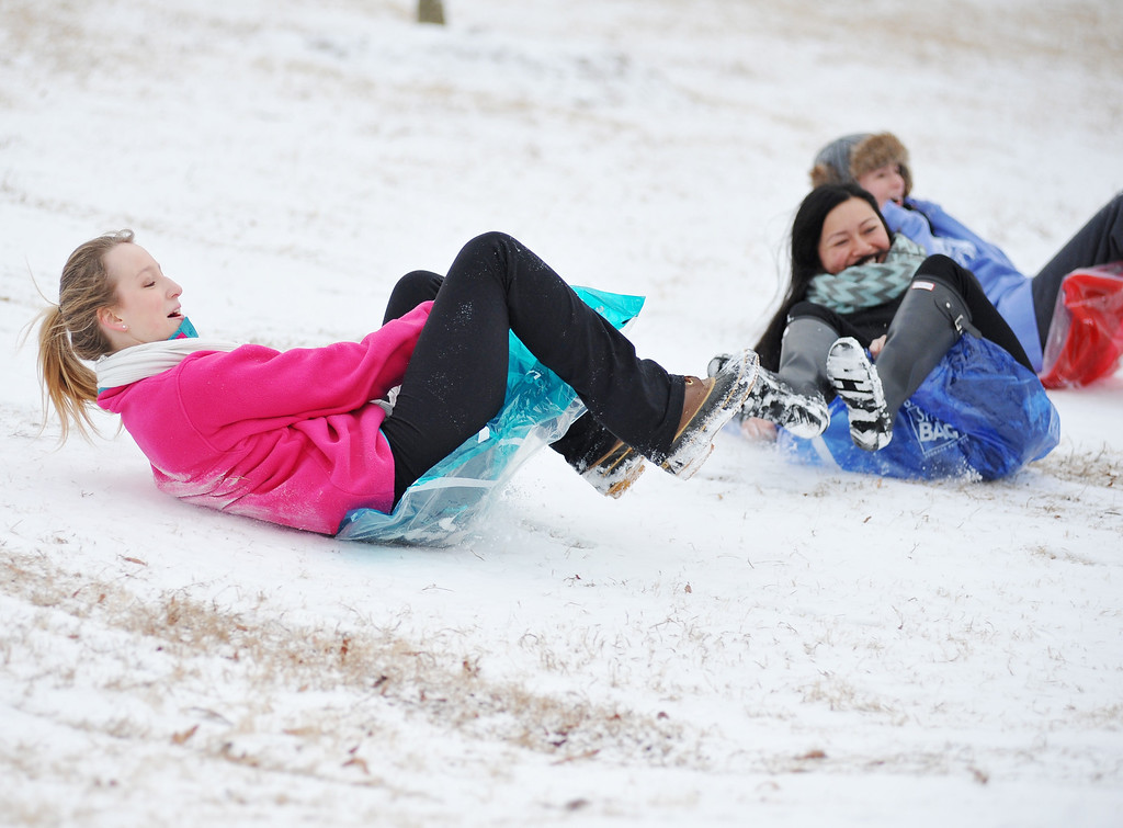 . University of Mississippi students Shelby Nordan, left, Nancy Truong, center, and Kathryn Davis slide down a hill, in Oxford, Miss. on Tuesday, Feb. 11, 2014. Due to a thin layer of ice covered by snow that fell overnight, the university is closed until noon Tuesday. (AP Photo/Oxford Eagle, Bruce Newman)