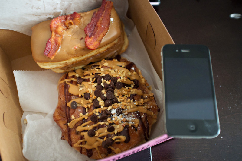 Bacon Maple Bar (above), with the Memphis Mafia, fried dough with banana chunks and cinnamon sugar covered in a glaze with chocolate frosting, peanut butter, peanuts and chocolate chips on top!    It's huge, my iPhone to the right as a reference of size.