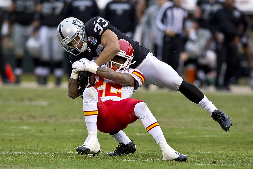 . Wide receiver Dexter McCluster #22 of the Kansas City Chiefs is tackled by strong safety Tyvon Branch #33 of the Oakland Raiders after a pass reception during the third quarter at O.co Coliseum on December 16, 2012 in Oakland, California. The Oakland Raiders defeated the Kansas City Chiefs 15-0. (Photo by Jason O. Watson/Getty Images)