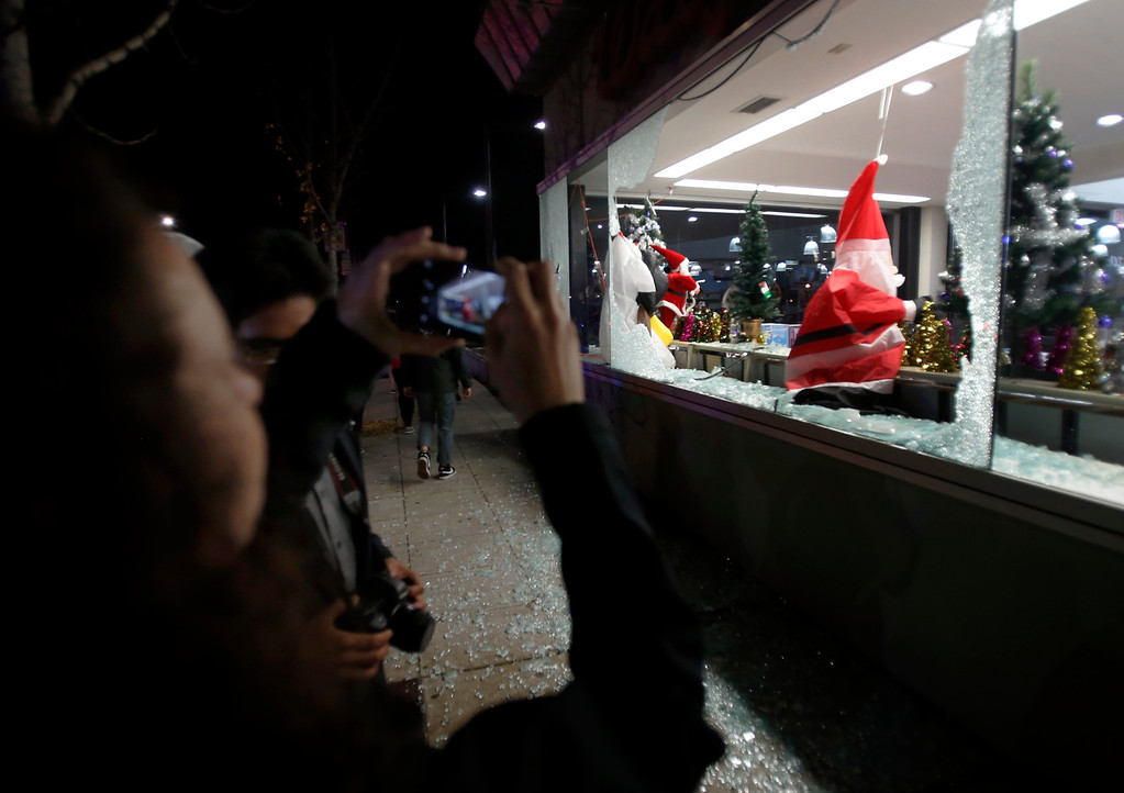 . A deflated Santa Claus decoration hangs in the broken window of a Shattuck Avenue drugstore in Berkeley, Calif., early Monday morning, Dec. 8, 2014, after a second wave of protesting over the killings of two unarmed black men by police in Ferguson, Mo., and New York. (Karl Mondon/Bay Area News Group)