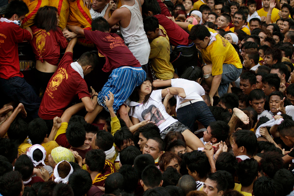 . A woman is pressed amongst devotees after touching the centuries-old image of the Black Nazarene during a raucous procession  Wednesday, Jan. 9, 2013, in Manila, Philippines. Hundreds of thousands of mostly barefoot Roman Catholic devotees joined the annual ritual to demonstrate faith and seek miracle cures for illnesses and a good life. (AP Photo/Aaron Favila)