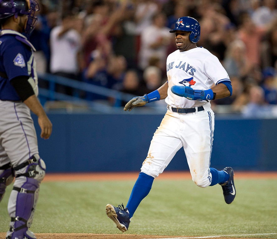 . Toronto Blue Jays Rajai Davis crosses the plate to scored what would be the game winning run in front of Colorado Rockies catcher Wilin Rosario in eight  inning of a baseball game in Toronto on Monday June 17, 2013.  (AP Photo/The Canadian Press, Frank Gunn)