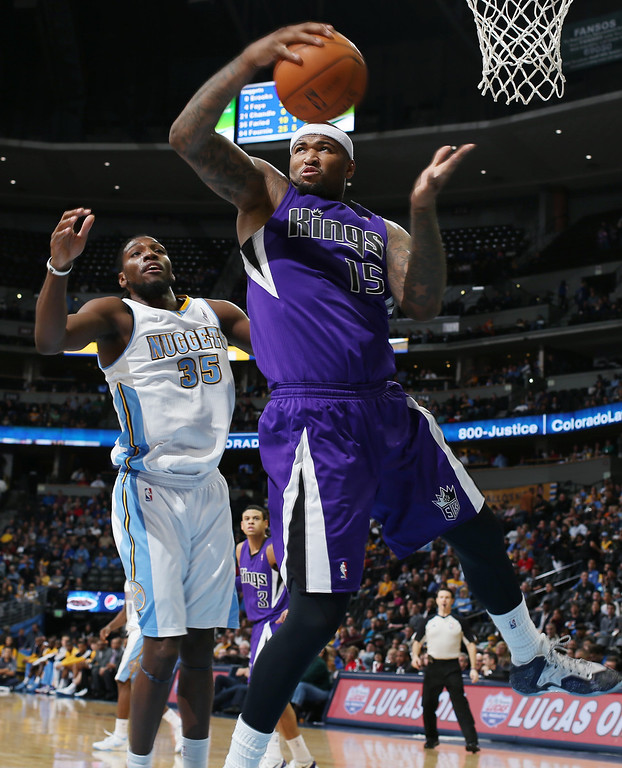 . Sacramento Kings center DeMarcus Cousins, center, pulls in rebound in front of Denver Nuggets forward Kenneth Faried in the fourth quarter of an NBA basketball game in Denver, Sunday, Feb. 23, 2014. The Kings won 109-95. (AP Photo/David Zalubowski)