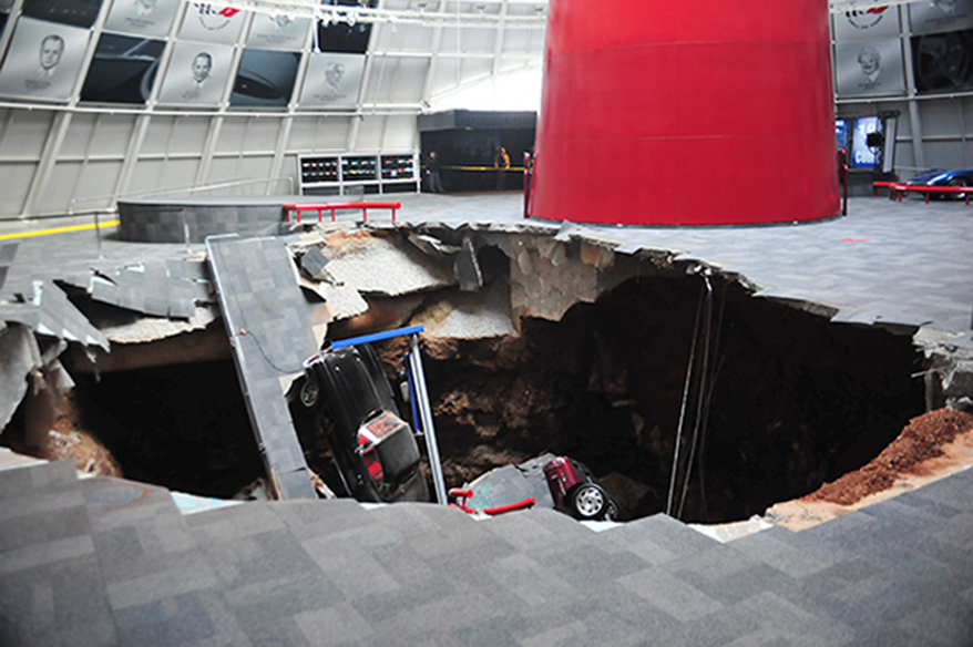 Description of . In this image provided by the National Corvette Museum shows several cars that collapsed into a sinkhole Wednesday, Feb. 12, 2014, in Bowling Green, Ky. The museum said a total of eight cars were damaged when a sinkhole opened up early Wednesday morning inside the museum. (AP Photo/National Corvette Museum, HO)