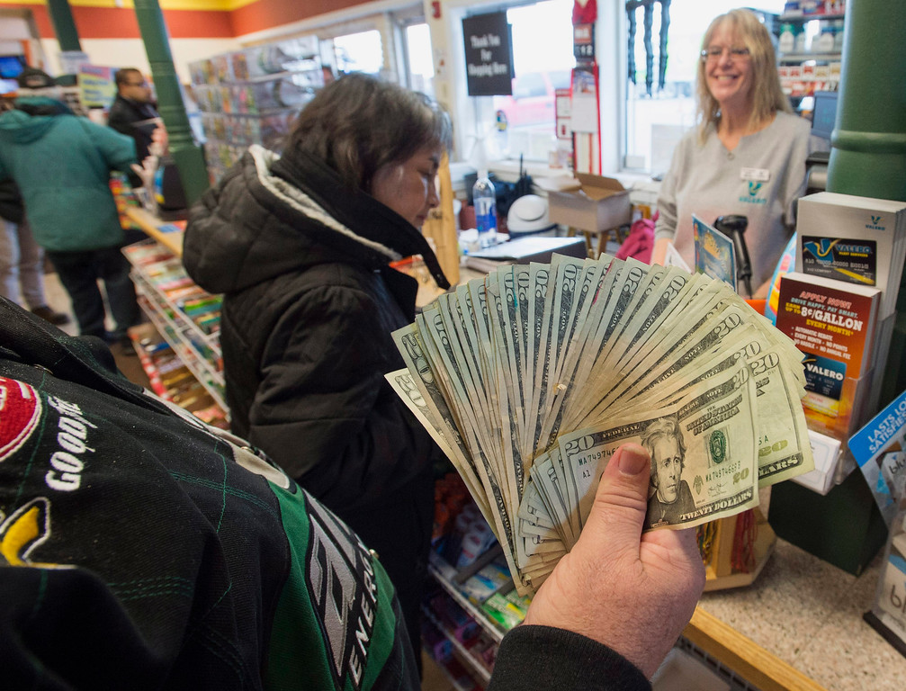 . Robert Charbonneau, from Saint-Donat, Quebec, waits to buy $1,000 worth of Powerball tickets for himself and his friends at a convenience store in the border town of Champlain, N.Y., Tuesday, Jan. 12, 2016. The jackpot lottery has reached a record setting of more than $1 billion. (Ryan Remiorz/The Canadian Press via AP)