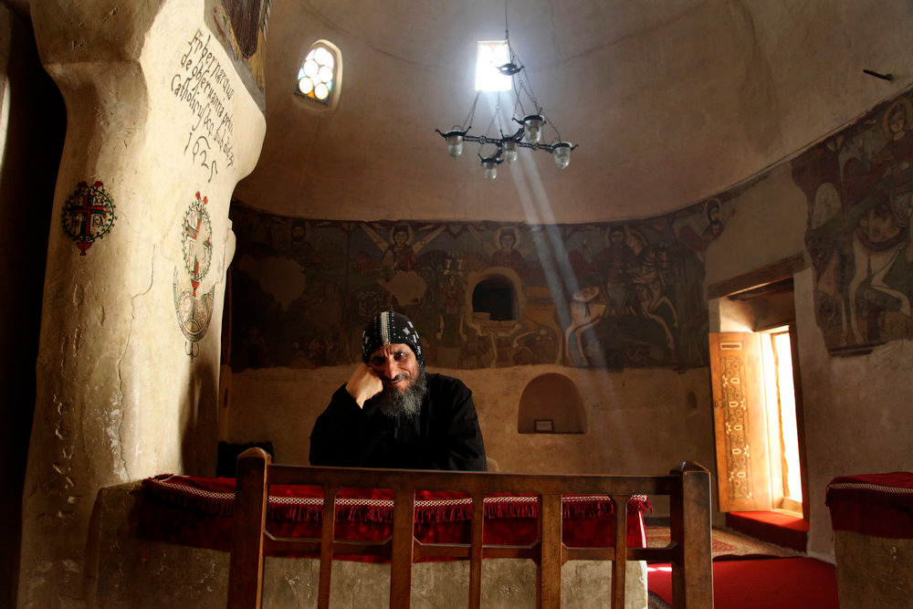 . A monk sits inside a chapel dating back to the fourth century at the ancient monastery of St. Anthony in the eastern desert southeast of Cairo, Egypt on Tuesday, April 16, 2013. In a cave high in the desert mountains of eastern Egypt, the man said to be the father of monasticism took refuge from the temptations of the world some 17 centuries ago. The monks at the St. Anthony\'s Monastery bearing his name continue the ascetic tradition. But even they are not untouched by the turbulent times facing Egypt\'s Christians, defiantly vowing their community\'s voice won\'t be silenced amid Islamists\' rising power. (AP Photo/Manoocher Deghati)