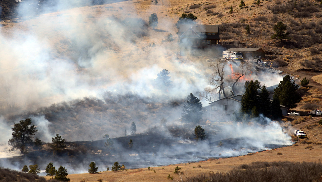 . Firefighters attack to keep a line during the fire that started near Lory State Park in Fort Collins, Colo. Friday March 15, 2013. The 40-acre wildfire burning in gusty winds and warm weather was threatening homes west of Fort Collins on Friday and prompted about 50 people to leave the area. (AP Photo/The Coloradoan, V. Richard Haro)