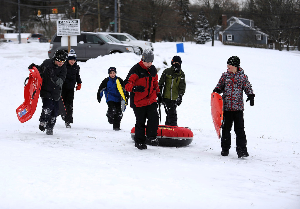 . A group of sledders arrive at Nelson\'s Field in Bristol, Conn.,  on Tuesday, Jan. 27, 2015.  A major winter storm dropped a foot of snow or more over much of Connecticut, hitting hardest in the eastern part of the state.  (AP Photo/The Bristol Press, Mike Orazzi)