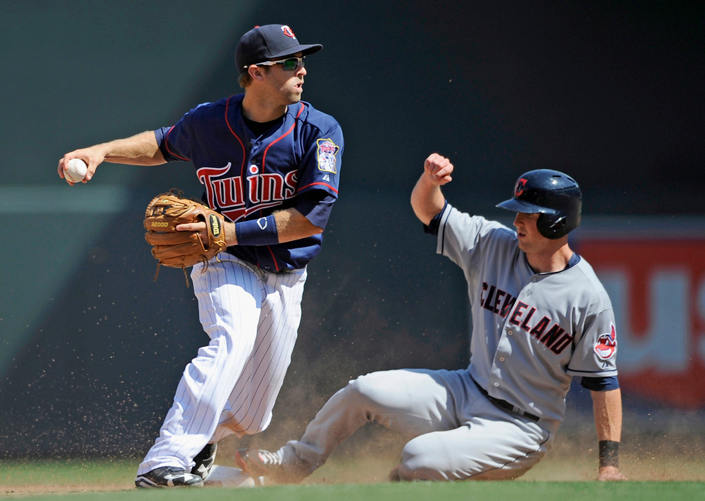 . Cleveland\'s Drew Stubbs is out at second base as Twins second baseman Brian Dozier relays to first but fails to turn a double play during the ninth inning. (Photo by Hannah Foslien/Getty Images)
