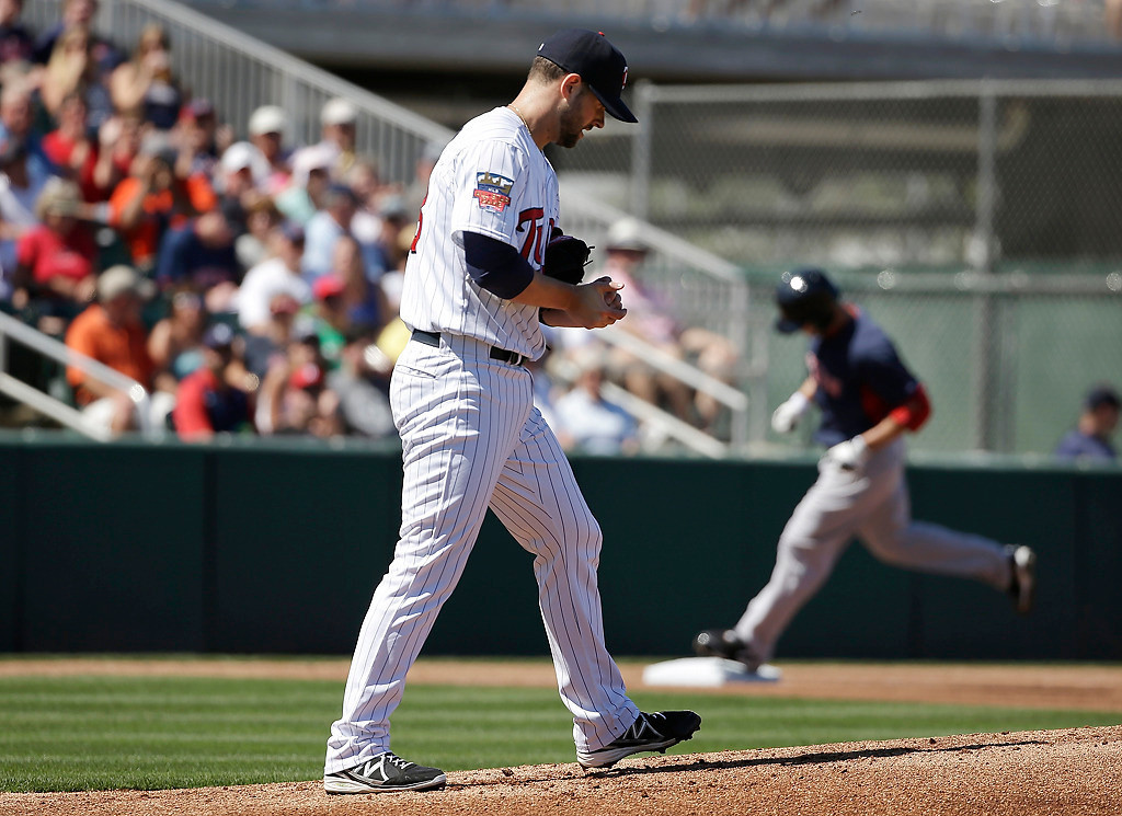 . Minnesota Twins starting pitcher Scott Diamond, left, steps onto the mound as Boston Red Sox\'s Daniel Nava, right, rounds the bases toward home after hitting a home run off Diamond in the first inning of an exhibition baseball game, Saturday, March 1, 2014, in Fort Myers, Fla. (AP Photo/Steven Senne)