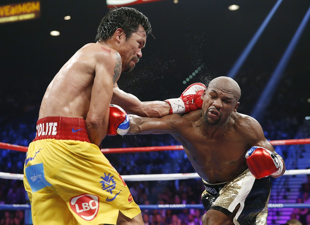 . Manny Pacquiao, from the Philippines, left, trades punches with Floyd Mayweather Jr., during their welterweight title fight on Saturday, May 2, 2015 in Las Vegas. (AP Photo/John Locher)