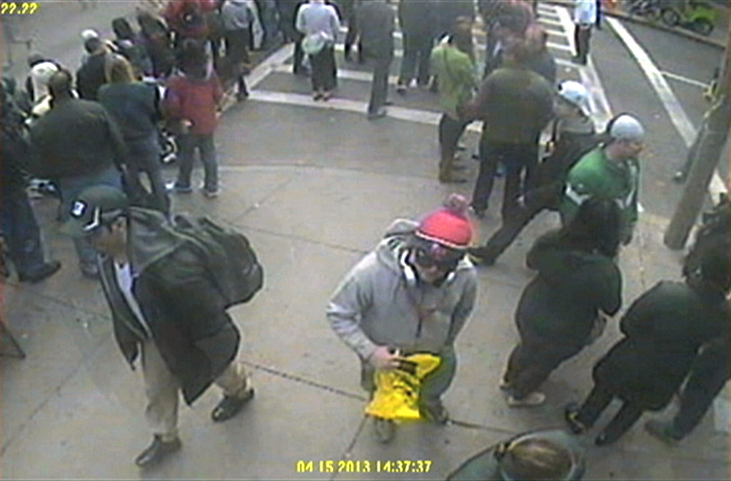. This image released by the FBI on Thursday, April 18, 2013, shows in a image from video what the FBI are calling suspect number 1, front left, in black cap, and suspect number 2, in white cap, back right, walking near each other through the crowd in Boston on Monday, April 15, 2013, before the explosions at the Boston Marathon. (AP Photo/FBI)